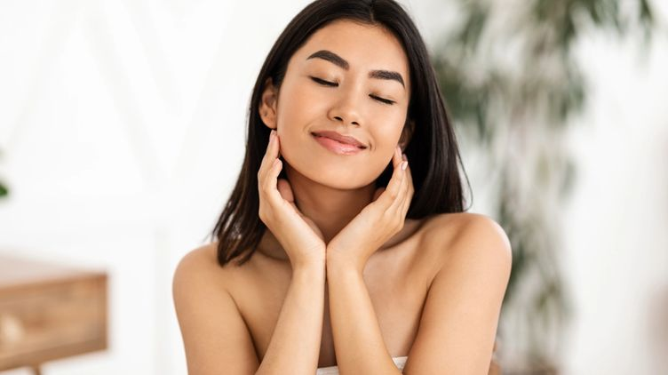 A beautiful Asian woman with eyes closed and hands on her chin