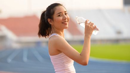Asian woman in pink tank top drinking water on a running track