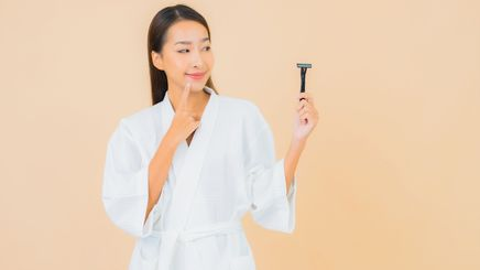 An Asian woman holding a razor with her left hand
