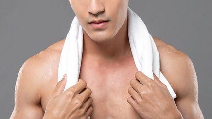 Shirtless man with white towel around neck