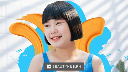 An Asian girl with a short bob smiling under the sun