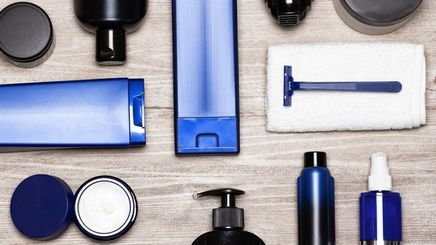 Several items for men's grooming kit arranged on a wooden table