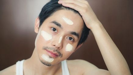 An Asian man with a mustache, beard, and face cream with his hand on his hair
