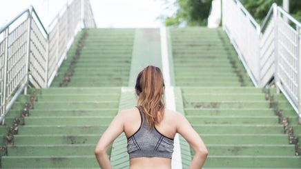 Asian woman in gray sports bra about to run up green stairs