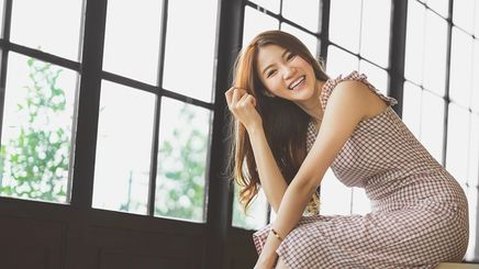 Happy Asian woman sitting on a bench