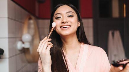 Asian woman doing her makeup