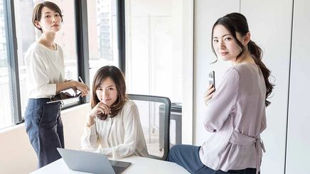 Three women pose for the camera in their office environment