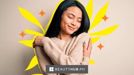 Asian woman wearing a beige sweater hugging herself.