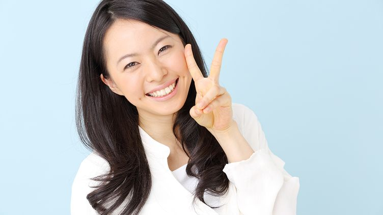 Smiling Asian making the peace sign against blue background