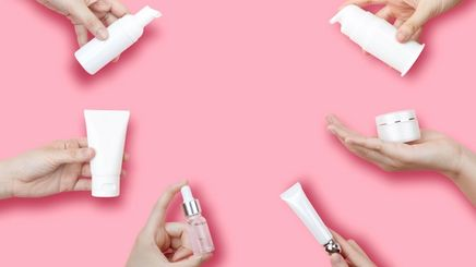 Six hands holding different skincare products