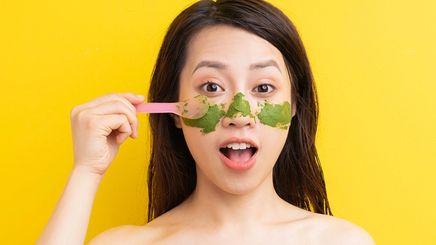 Woman applying a green mask on skin