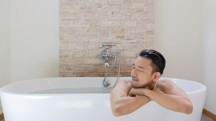 An Asian man relaxing in the bathtub.