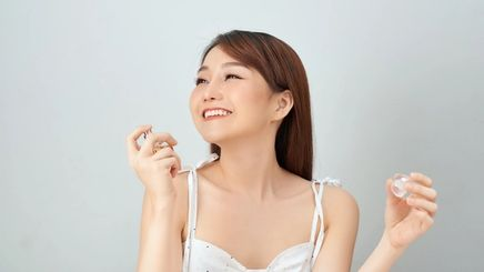 A smiling young woman applying perfume