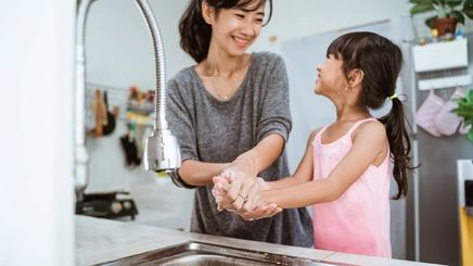 Asian mother and daughter washing hands in the kitchen