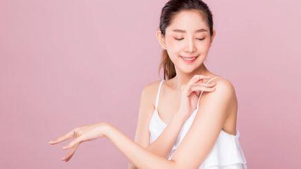 A woman touching her skin.