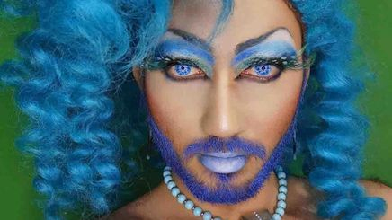 Portrait of a young drag queen in full makeup and blue hair