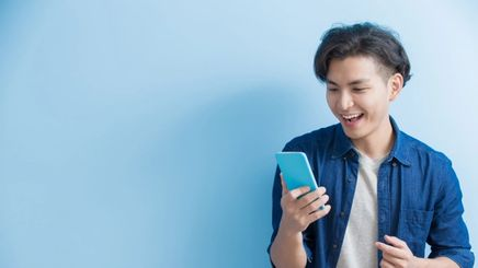 Man laughing holding a phone.