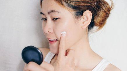 Young Asian woman applying serum on cheek