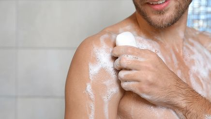 A man bathing holding soap in one hand