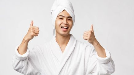 An Asian man in a white bathrobe and towel throwing two thumbs-ups in the air