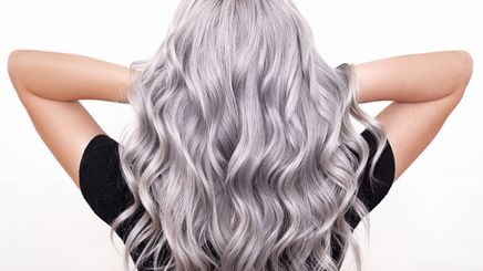 A woman with long, wavy grey hair