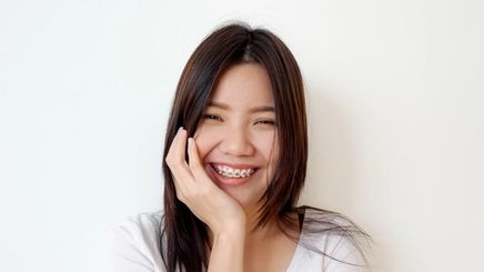 a woman with braces touching her face