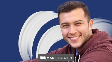 Handsome smiling Asian man in maroon hoodie sitting outdoors
