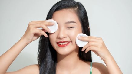 A young Asian girl holding cotton pads to her face.