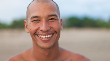 Asian man in his 30s smiling at the beach