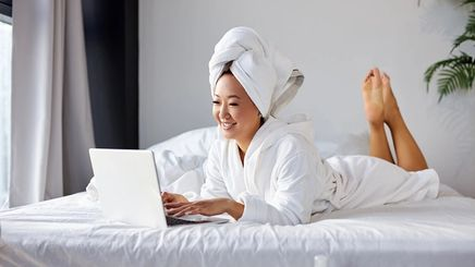 Asian man on bed with towel around head and smiling at laptop