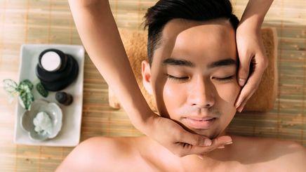 An Asian man getting a face massage
