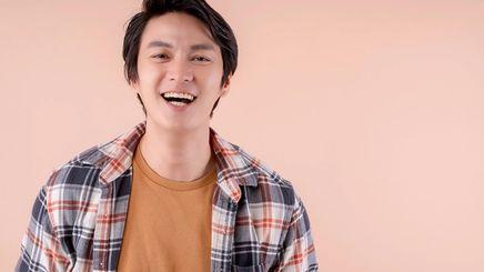 Asian man in plaid smiling