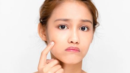 Young Asian woman touching her face with a finger