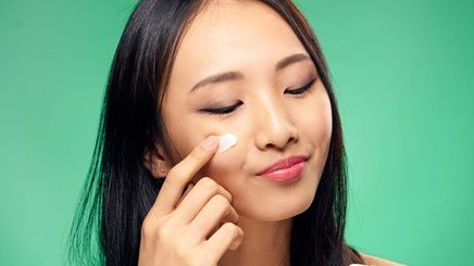 An Asian woman applying a cream under her eyes