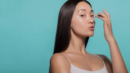 A woman applying a face moisturizer