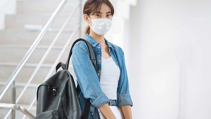 Asian woman wearing a mask and carrying a black knapsack
