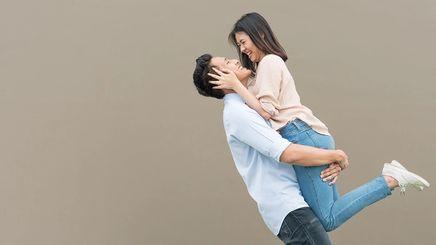 Asian man carrying girlfriend