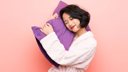 Asian woman in a robe holding a purple pillow