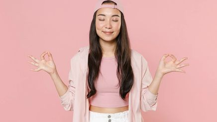 Smiling young woman holds her hands in yoga gesture