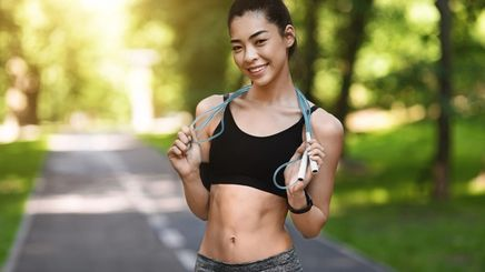 Fit Asian woman holding a jump rope around her neck