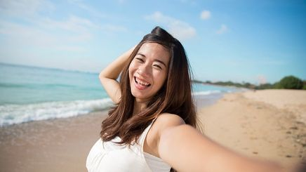 Happy Asian woman at the beach