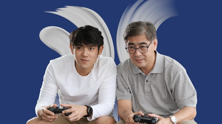 An Asian father and son sitting on a couch, playing video games