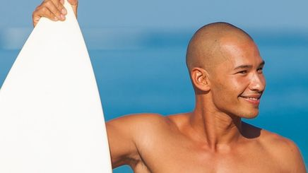 Young man with a shaved head holding a surfboard on the beach