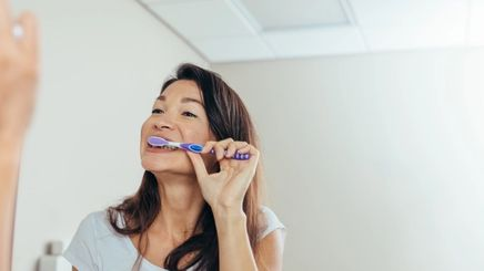 Woman looking at the mirror brushing her teeth with a toothpaste.