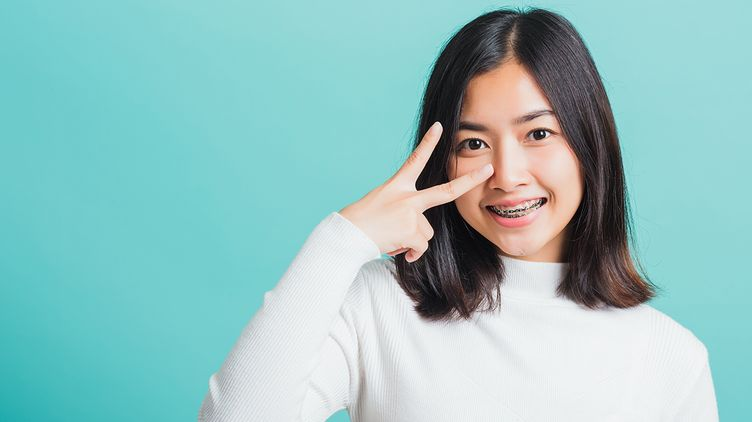 Asian woman with flyaway shoulder-length hair and holding a V-sign with fingers