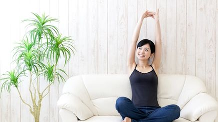 A beautiful Asian woman stretching her arms on a couch