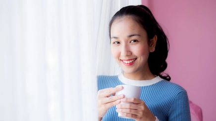 woman smiling while drinking coffee