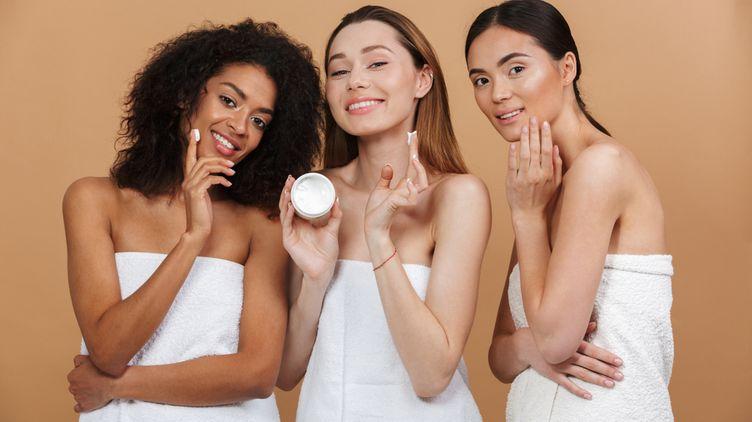 Diverse women applying moisturizer.