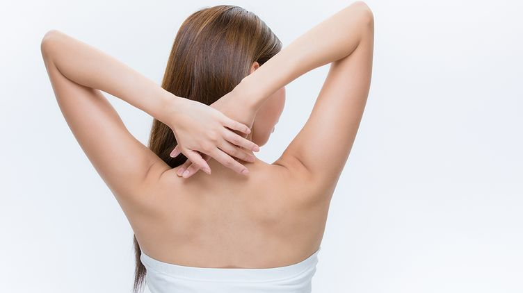 Woman with her hands on her nape and back exposed