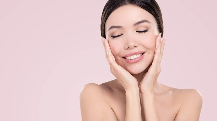 A smiling Asian woman touching her face